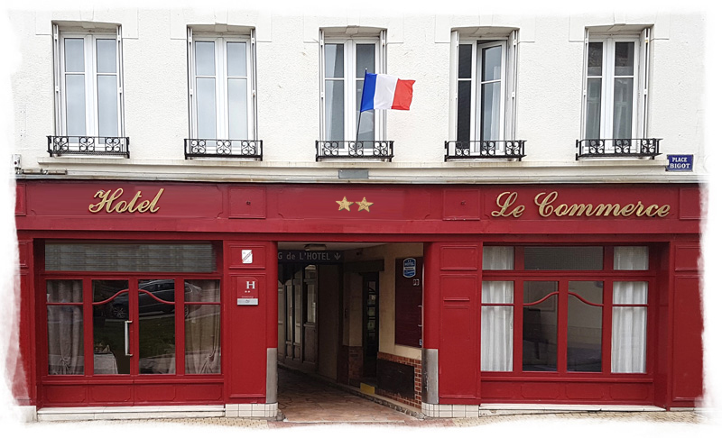 The red wooden facade of the Hotel in Fécamp with the French flag